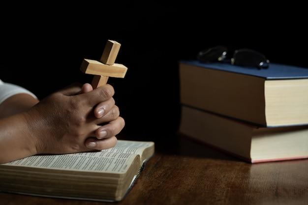 Hände, die zu gott beim halten des kreuzsymbols beten.