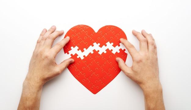 Hände, die zwei puzzleteile in form des herzens auf weiß zusammenbringen