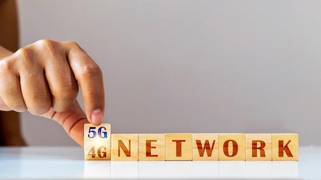 Hände drehen den würfel der 4g-zahlen zu 5g, dem konzept des 5g-netzes und der anbindung zukünftiger funktechnologie.