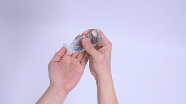 Hände drückt alkoholhandgel auf weißem hintergrund.