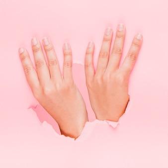 Hände durch ein papierloch
