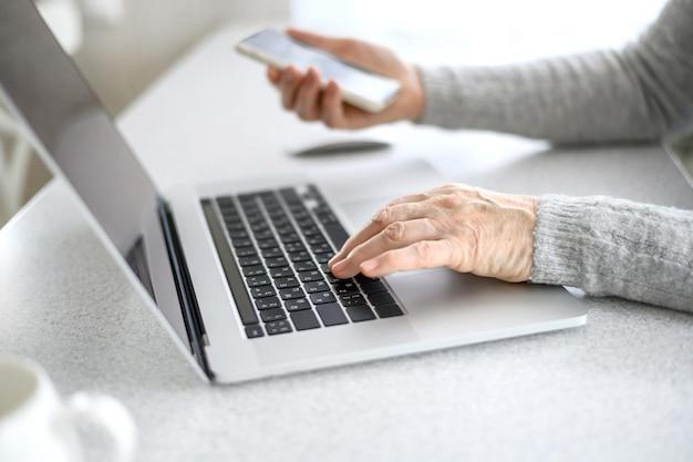 Hände einer älteren frau arbeiten an einem laptop mit einem telefon unter verwendung moderner technologie im täglichen leben.