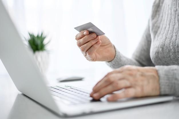 Hände einer älteren frau arbeiten an einem laptop mit kreditkarte unter verwendung moderner technologie im täglichen leben. online einkaufen.