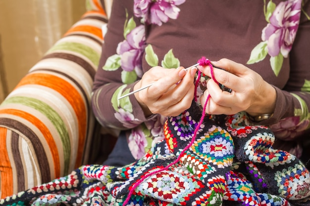 Hände einer älteren frau, die eine vintage-wolldecke mit bunten flecken strickt