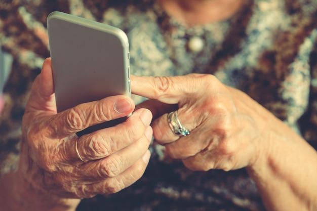 Hände einer älteren frau, die einen handy hält