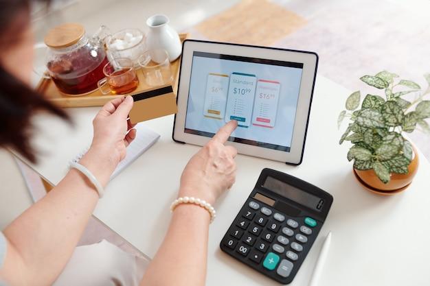 Hände einer älteren frau, die einen serviceplan auf einem digitalen tablet wählt und mit kreditkarte bezahlt