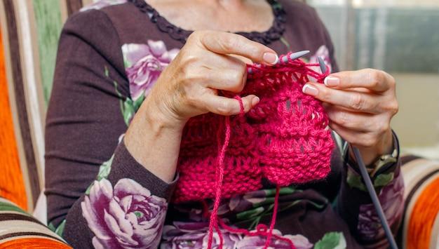 Hände einer älteren frau, die zu hause einen wollpullover strickt