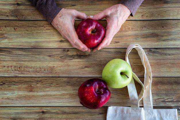Hände einer alten frau, die frischen organischen apfel hält. eco einkaufstasche auf hölzernem hintergrund