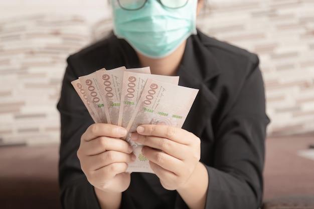 Hände einer frau, die eine banknoten hält, belaufen sich auf 5.000 baht thailand