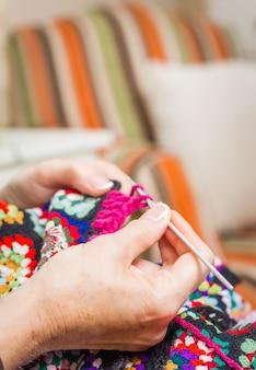 Hände einer frau, die eine vintage-wolldecke strickt