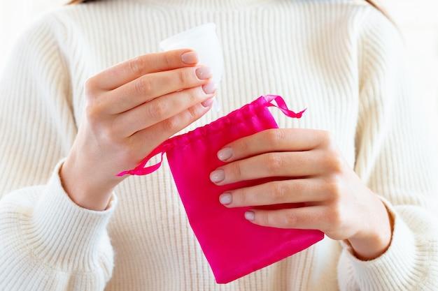 Hände einer frau, die menstruationstasse in eine tasche setzen