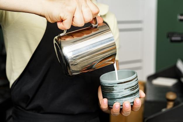 Hände einer frau, die milch in eine tasse gießt