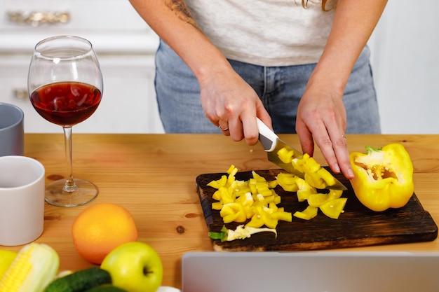 Hände einer frau, die paprika auf hölzernem schneidebrett schneidet