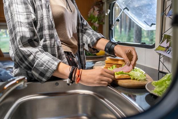 Hände einer frau, die speck und salat auf ein stück brot legt