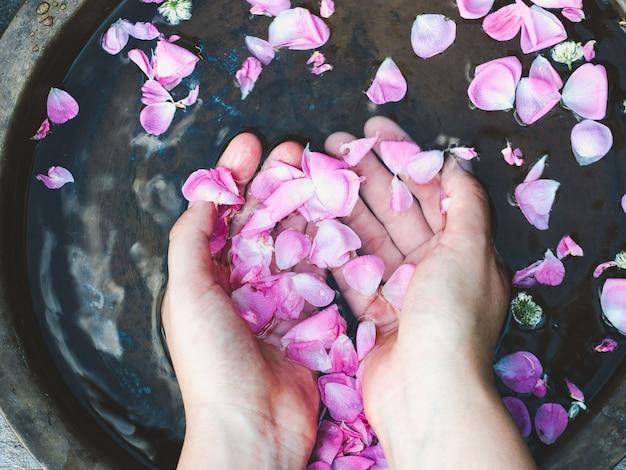 Hände einer frau, rosenblätter