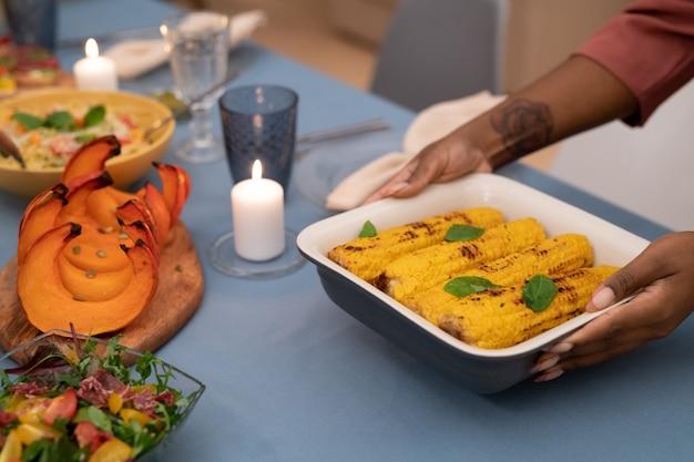 Hände einer jungen afrikanerin, die eine schüssel mit gegrilltem mais auf einen festlichen tisch neben brennender kerze, gebackenem kürbis und gemüsesalat stellt
