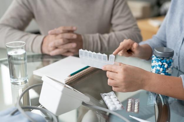 Hände einer jungen frau, die auf medizin zeigt, während sie ihrem alten pensionierten vater hilft, mit dem zeitplan für die einnahme von pillen fertig zu werden