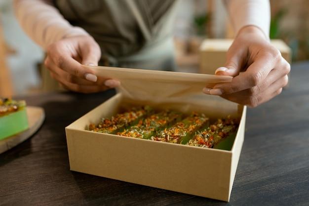 Hände einer jungen frau, die frische handgemachte naturseife in eine karton-geschenkbox verpackt, während sie vor dem urlaub geschenke für ihre freunde vorbereitet