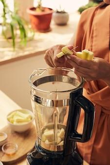 Hände einer jungen frau, die frische zucchini in einen elektrischen mixer schneidet