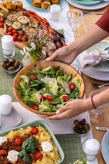 Hände einer jungen frau, die schüssel mit vegetarischem salat auf den servierten tisch stellt