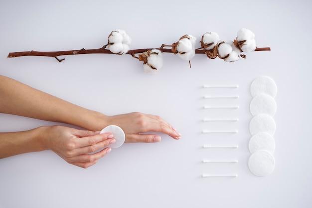 Hände einer jungen frau mit einem baumwollzweig, wattepads und wattestäbchen auf einem weißen hintergrund. weibliche maniküre. baumwollblume. spa-konzept. kreative komposition mit baumwolle.