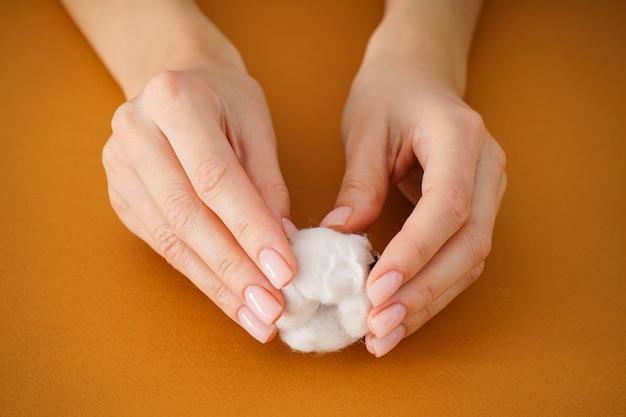 Hände einer jungen frau mit einer blume der baumwolle auf einem beigen hintergrund. weibliche maniküre. nahansicht.