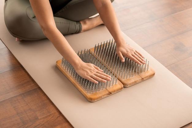 Hände einer jungen frau mit gekreuzten beinen in aktivkleidung, die während der konzentrationsübung mit den handflächen auf yoga-pads mit nägeln auf der matte sitzt