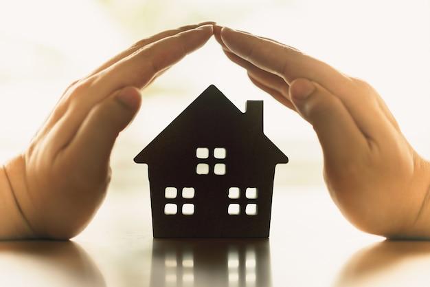 Hände einer jungen frau umgeben ein hölzernes hausmodell. immobilienmakler bieten haus