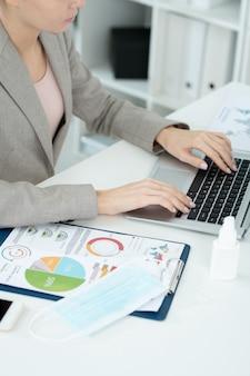 Hände einer jungen zeitgenössischen geschäftsfrau oder sekretärin im eleganten grauen anzug, die die tasten der laptop-tastatur während der vernetzung im büro drückt