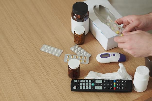 Hände einer kranken person, die schmerzmittel, antipyretika oder andere pillen vom tisch nimmt, während sie wegen einer krankheit während einer covid19-pandemie zu hause bleibt
