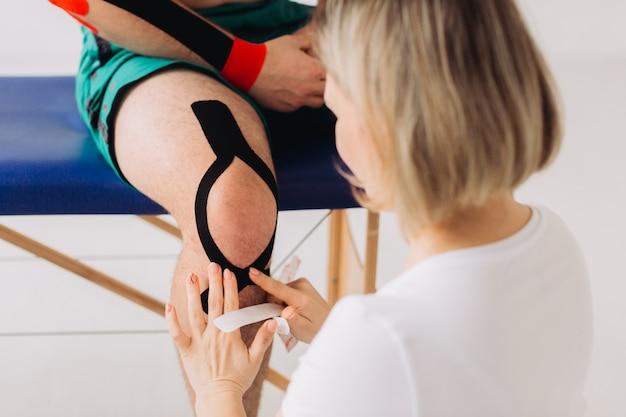 Hände einer physiotherapeutin, die rotes medizinisches klebeband auf ein anderes schwarzes farbband auf das knie eines patienten klebt.