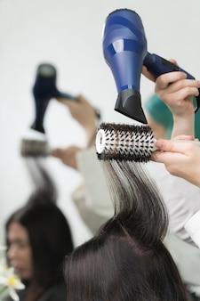 Hände einer professionellen kosmetikerin trocknen lange brünette haare des kunden mit blauem fön und weißer haarbürste im schönheitssalon.