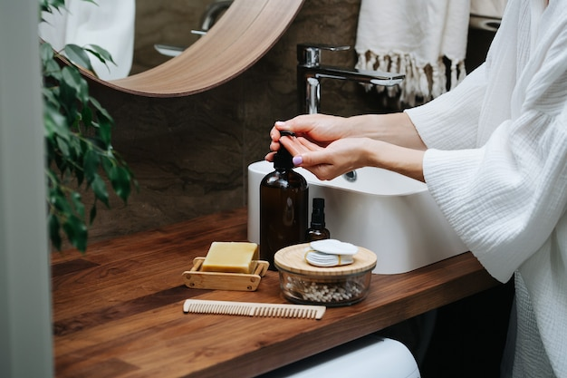 Hände einer reifen frau, die eine öko-seife aus einer flasche pumpt. sie steht in einem badezimmer vor dem waschbecken.