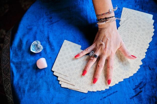 Hände einer reifen frau mit tarotkarten - unvorhersehbares zukunftskonzept