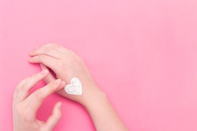 Hände einer schönen gepflegten frau mit einem cremefarbenen glas auf einem rosa strukturierten hintergrund.