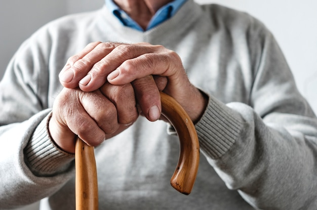 Hände eines älteren mannes, der auf einem gehenden stock stillsteht