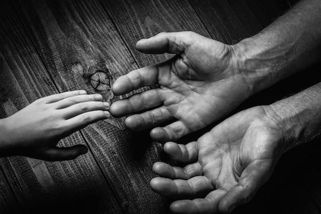 Hände eines älteren mannes, der die hand eines jüngeren mannes hält. viel textur und charakter in den händen des alten mannes. auf schwarzer holzwand. schwarz und weiß.