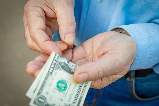 Hände eines älteren mannes mit einem us-dollar und einem cent