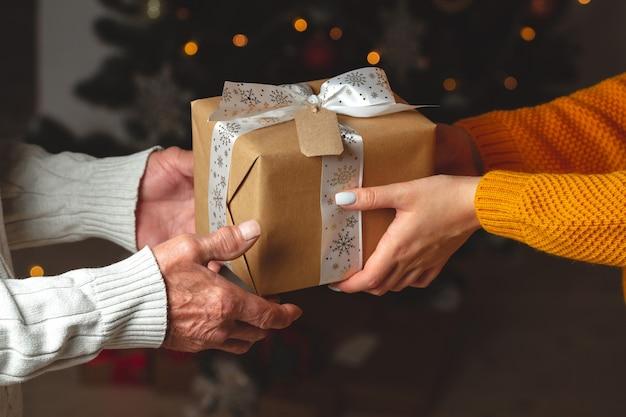 Hände eines älteren senors und einer jungen frau geben ein weihnachtsgeschenk