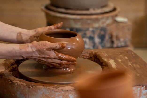 Hände eines älteren töpfers, der mit ton auf einer töpferscheibe arbeitet