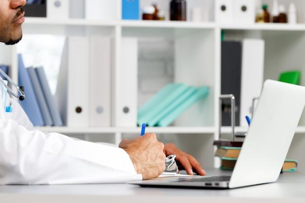 Hände eines arztes, der etwas in zwischenablage schreibt, während er am arbeitstisch nah sitzt