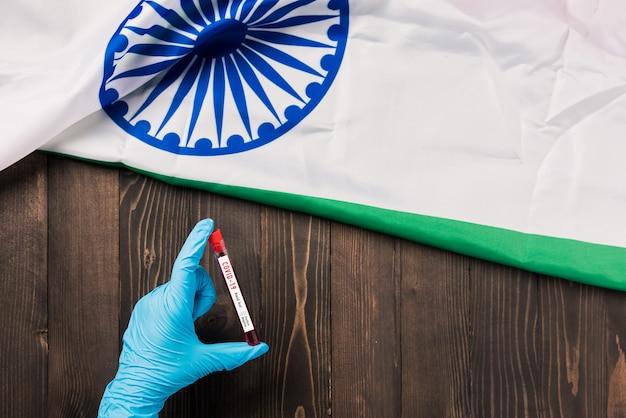 Hände eines arztes, der handschuhe trägt, die blut-reagenzglas-coronavirus (covid-19) -virus im labor mit der flagge indien halten