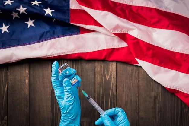Hände eines arztes, der handschuhe trägt, die coronavirus-fläschchenimpfstoff und spritze mit flagge vereinigte staaten von amerika halten