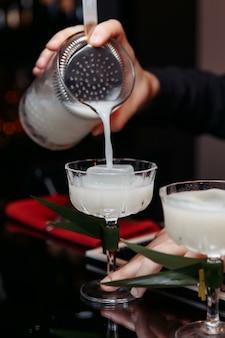 Hände eines barkeepers, der einen shaker hält, der ein getränk in ein glas gießt.