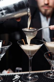 Hände eines barkeepers, der einen shaker hält, der ein getränk in ein martini-glas gießt.