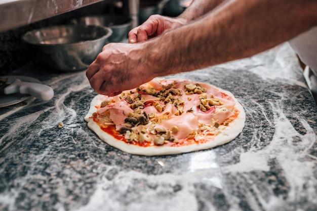 Hände eines chefs, der pizza zubereitet.