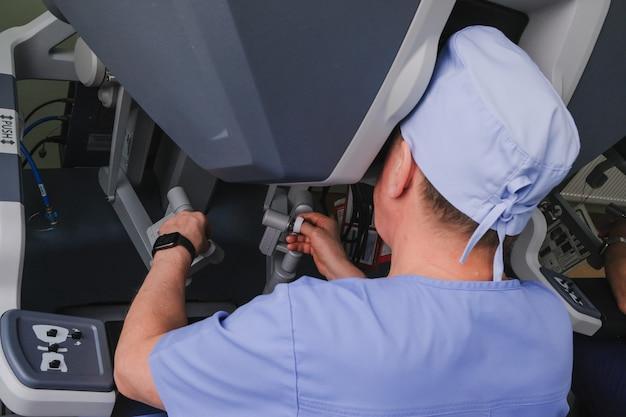 Hände eines chirurgen, der einen chirurgischen roboter bedient, den prozess der durchführung einer operation mit einem modernen robotergestützten chirurgischen system