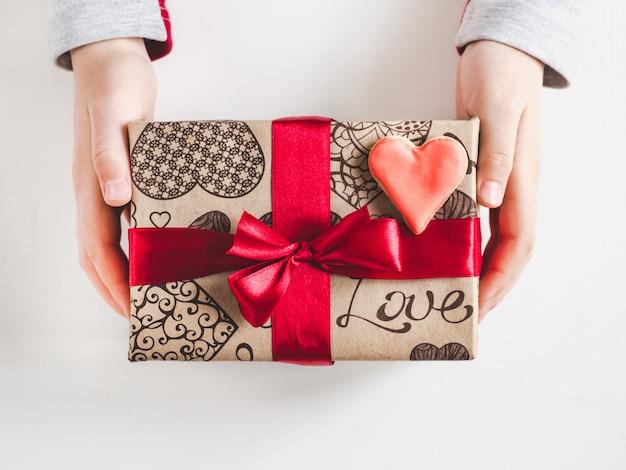 Hände eines elternteils und eines kindes, kasten mit einem geschenk