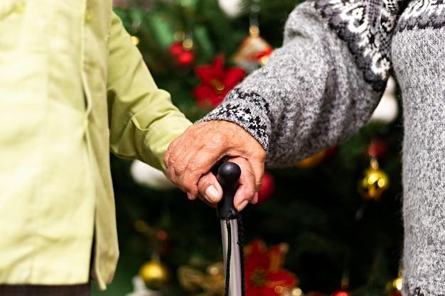 Hände eines erwachsenen paares, das einen stock vor dem weihnachtsbaum hält