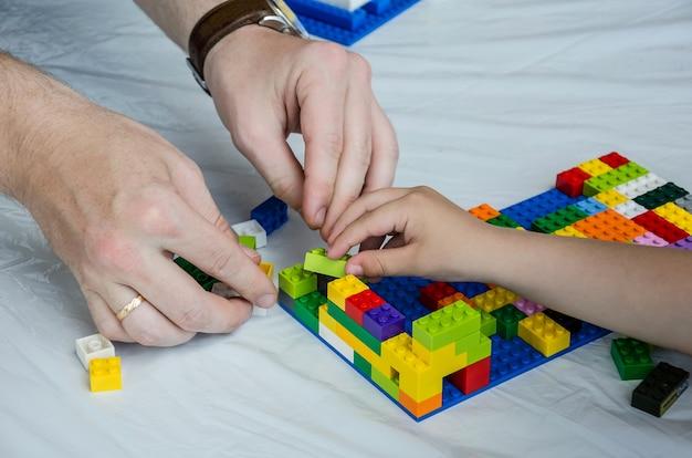 Hände eines erwachsenen und eines kinderspielkonstrukteurs.